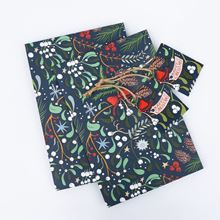 Two sheets of Midnight mistletoe design wrapping paper and two twine tie tags